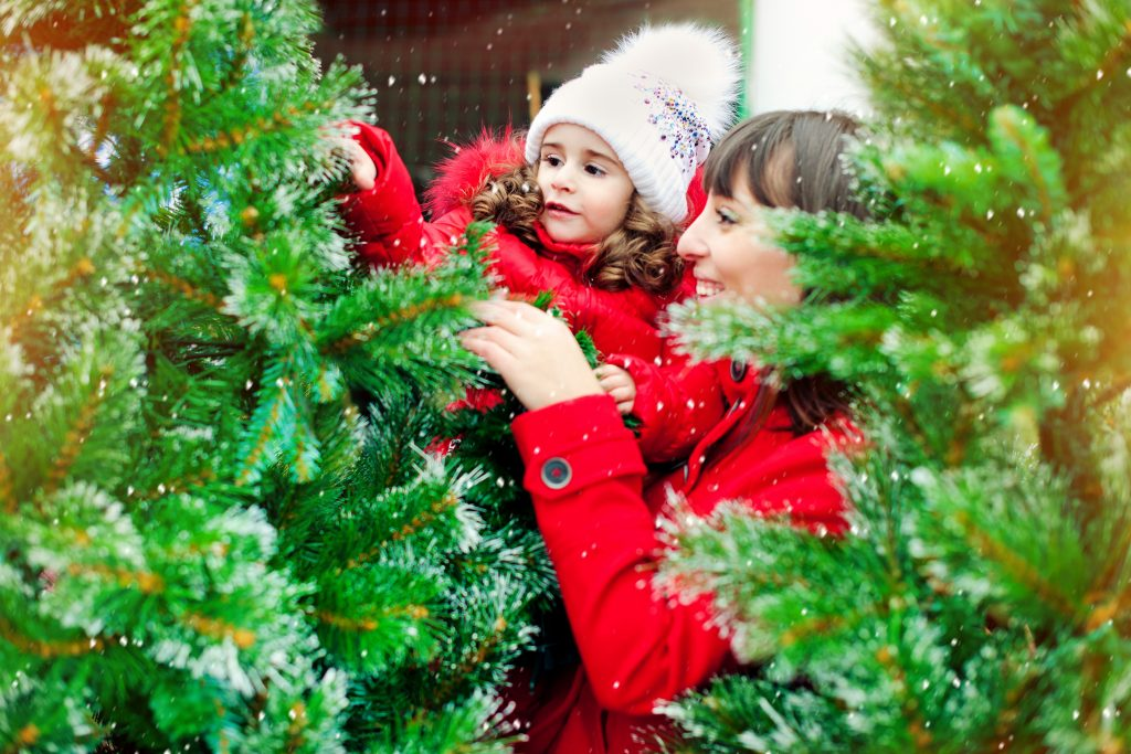 woman and child decorating a pine tree